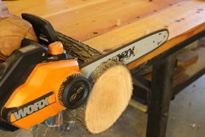 Use a chainsaw to create round disc for both ends of the log bird feeder.